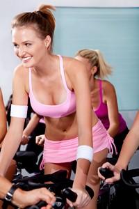 健身单车上的美丽性感女子高清图片下载