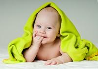 盖着绿色毛巾的婴儿高清图片下载