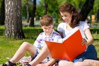 草地上看书的男孩与母亲高清图片下载